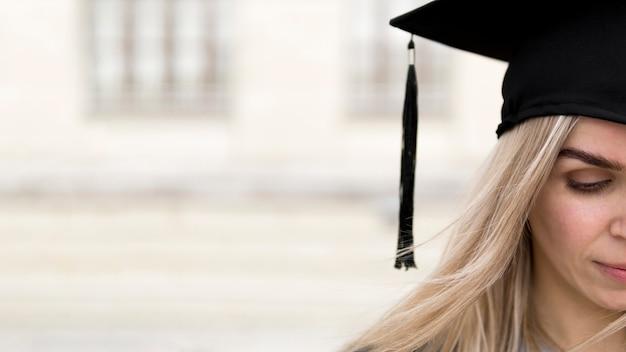 Jonge vrouw die een graduatie glb met exemplaarruimte draagt Gratis Foto