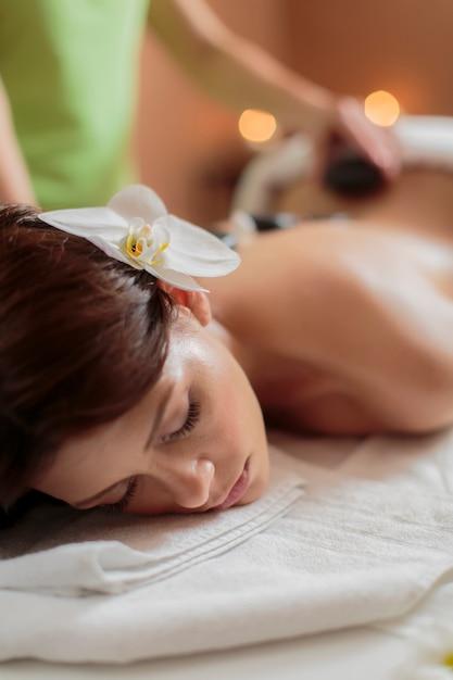Jonge vrouw die een hete therapie van de steenmassage heeft Premium Foto