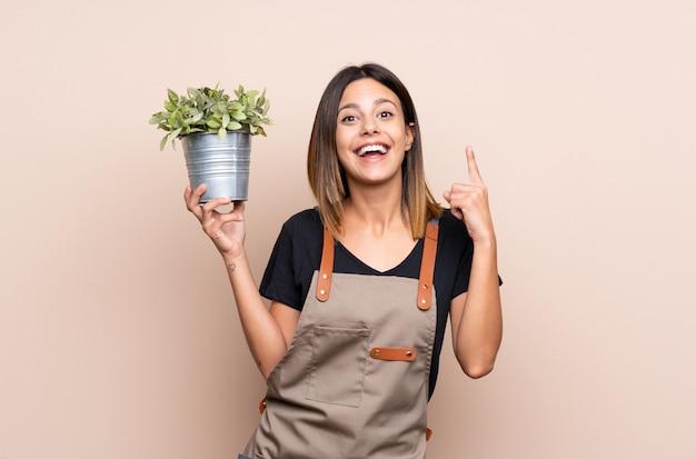 Jonge vrouw die een installatie houdt die een groot idee benadrukt Premium Foto