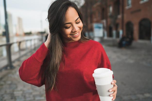 Jonge vrouw die een kop van koffie houdt. Gratis Foto