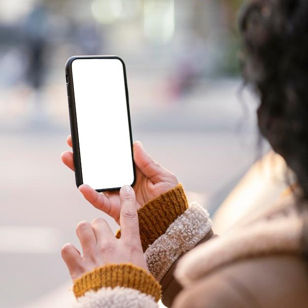 Jonge vrouw die een lege schermsmartphone controleert Gratis Foto