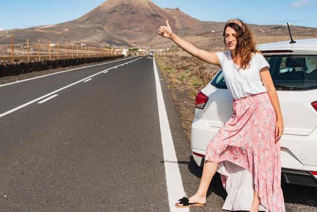 Jonge vrouw die een lekke band heeft gehad in een autowiel die met opgeheven duim lift Premium Foto