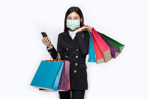 Jonge vrouw die een masker draagt en op haar smartphone winkelt Gratis Foto