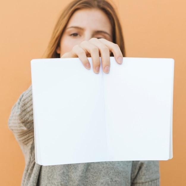 Jonge vrouw die een open wit boek voor camera houdt Gratis Foto