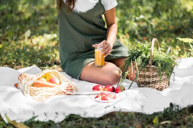 Jonge vrouw die een picknick met gezonde snacks heeft Gratis Foto