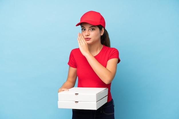 Jonge vrouw die een pizza over geïsoleerde roze muur houdt die iets fluistert Premium Foto