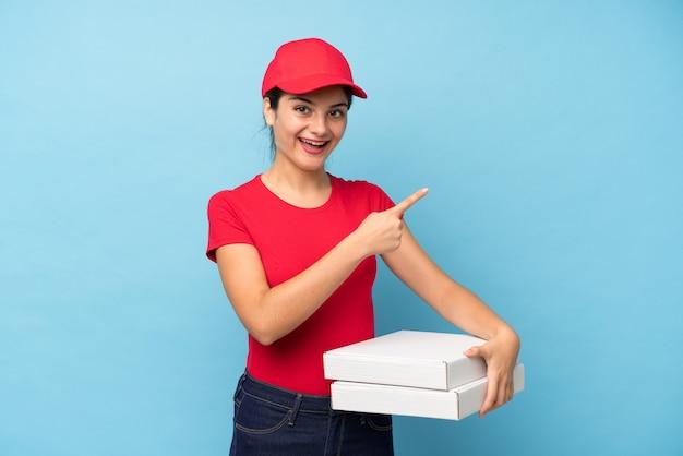 Jonge vrouw die een pizza over geïsoleerde roze muur houdt die vinger aan de kant richt Premium Foto