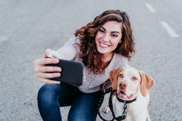 Jonge vrouw die een selfie met mobiele telefoon met haar hond bij de straat neemt Premium Foto
