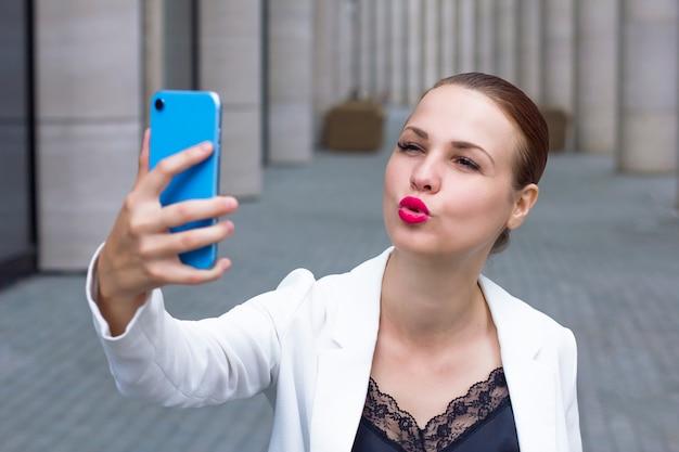Jonge vrouw die een selfie op smartphone neemt. Premium Foto
