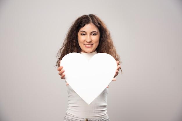 Jonge vrouw die een wit met de hand gemaakt document hart geeft. hoge kwaliteit foto Gratis Foto