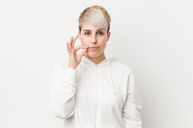 Jonge vrouw die een witte hoodie met vingers op lippen draagt die een geheim houden. Premium Foto