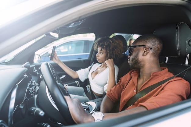 Jonge vrouw die een zelfportret met haar vriend in een auto neemt Premium Foto