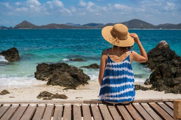 Jonge vrouw die en bij het tropische strand, de zomervakantie en het reisconcept ontspannen genieten van Premium Foto