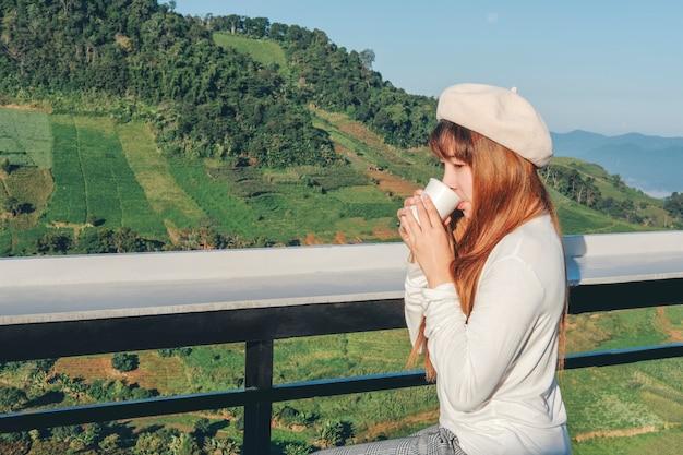 Jonge vrouw die en het drinken koffie op bergkoffie ontspant Premium Foto