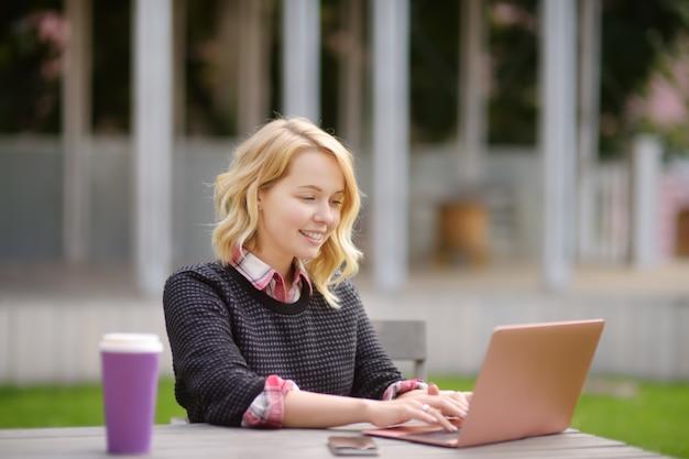 Jonge vrouw die / en van mooie dag bestudeert werkt werkt Premium Foto