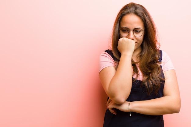 Jonge vrouw die ernstig, nadenkend en bezorgd voelt, zijdelings starend met hand die tegen kin tegen roze achtergrond wordt gedrukt Premium Foto
