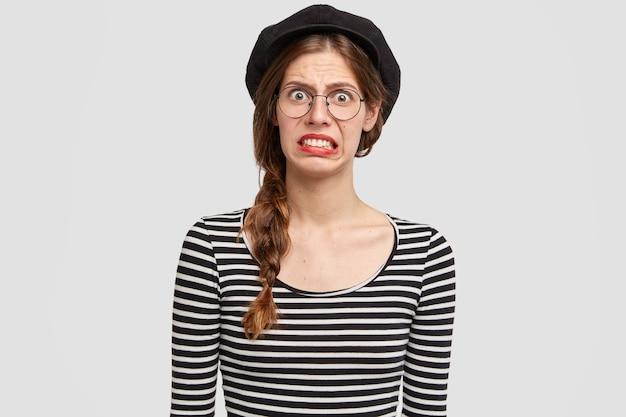 Jonge vrouw die gestreept overhemd en baret draagt Gratis Foto