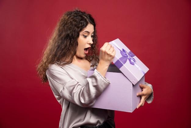 Jonge vrouw die giftdoos bekijkt en verrast wordt. Gratis Foto