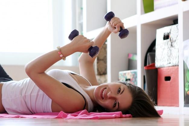 Jonge vrouw die gymnastiek- oefeningen doet Gratis Foto