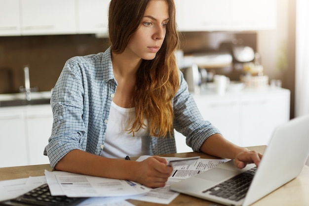 Jonge vrouw die haar begroting controleert en belastingen doet Gratis Foto