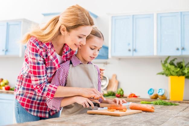Jonge vrouw die haar dochter helpt die de wortel met mes op houten lijst snijdt Gratis Foto