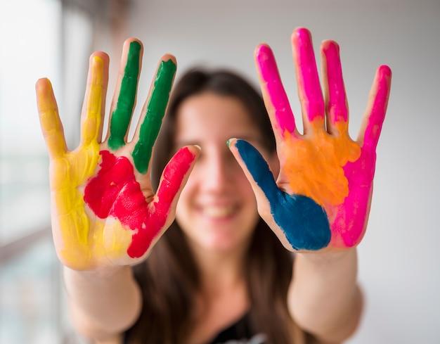 Jonge vrouw die haar geschilderde handen toont Gratis Foto