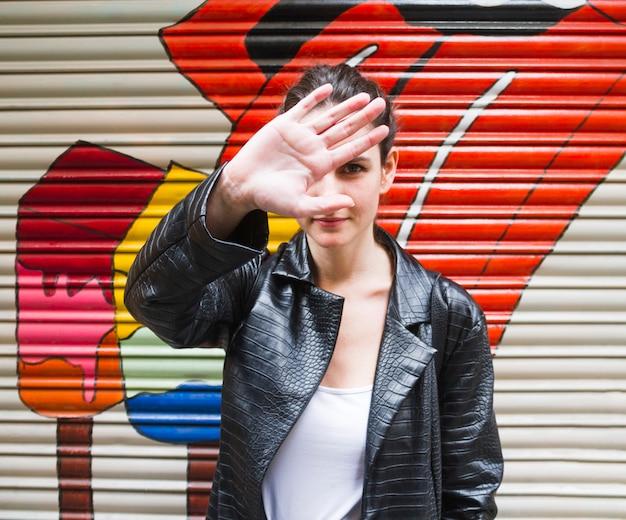 Jonge vrouw die haar gezicht met hand verbergt Gratis Foto