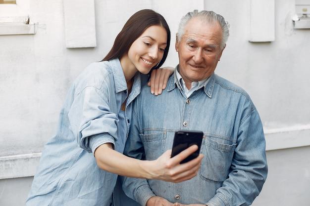 Jonge vrouw die haar grootvader onderwijst hoe te om een telefoon te gebruiken Gratis Foto