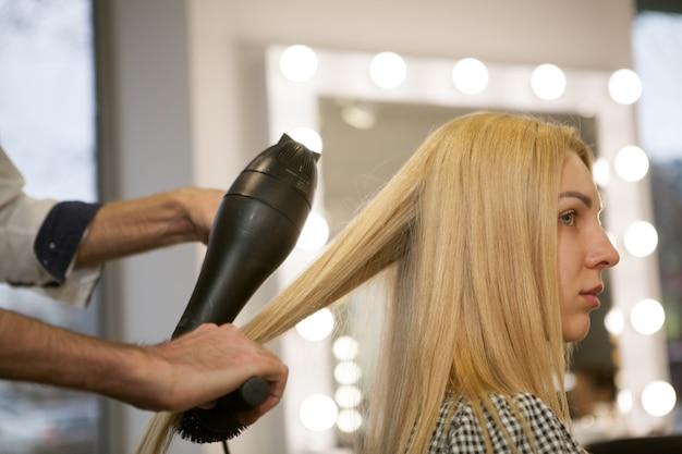 Jonge vrouw die haar haar heeft dat door kapper wordt gestileerd Premium Foto