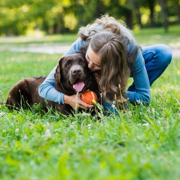 Jonge vrouw die haar hond in park kust Gratis Foto
