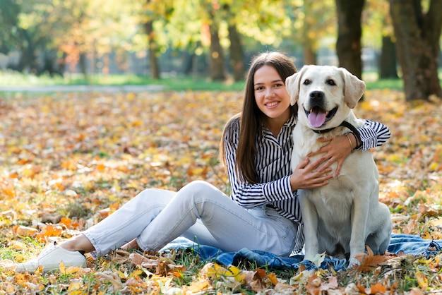 Jonge vrouw die haar hond koestert Gratis Foto