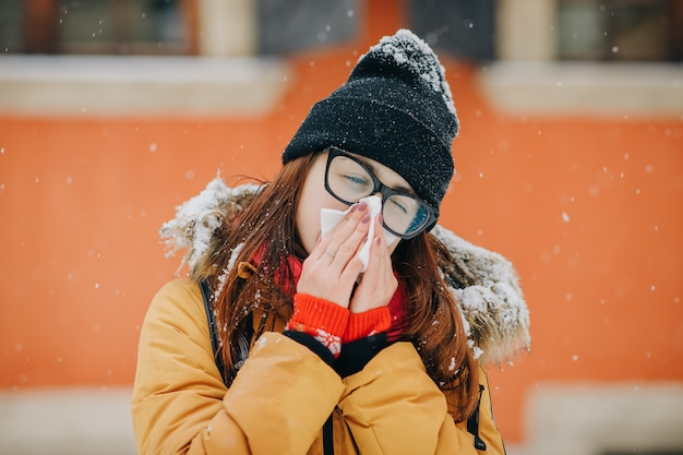 Jonge vrouw die haar neus in een weefsel in de winter blaast Premium Foto