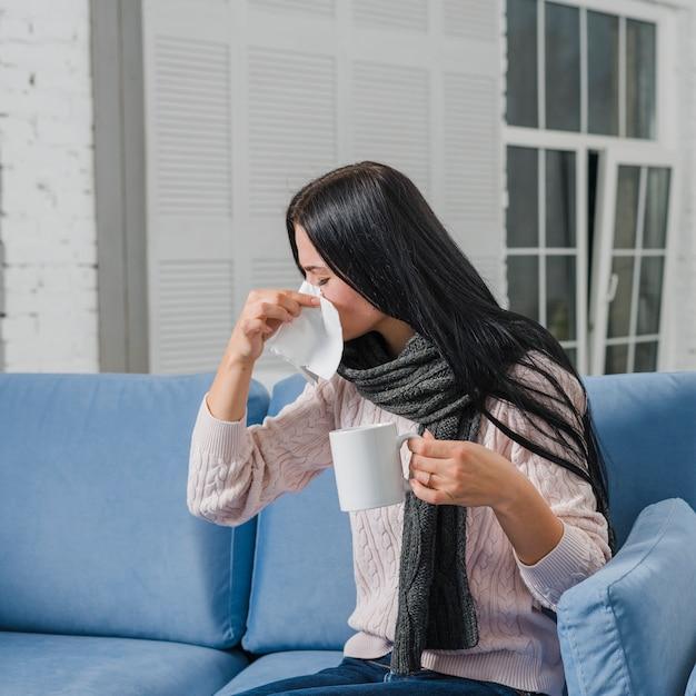 Jonge vrouw die haar neus met de koffiemok van de papieren zakdoekjeholding ter beschikking blaast Gratis Foto