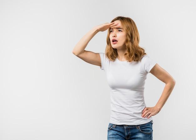 Jonge vrouw die haar ogen met hand op heupen beschermen tegen witte achtergrond Gratis Foto