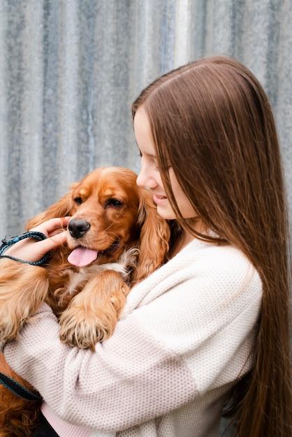 Jonge vrouw die haar puppy houdt Gratis Foto