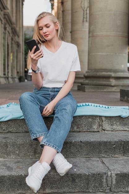 Jonge vrouw die haar telefoon controleert Gratis Foto
