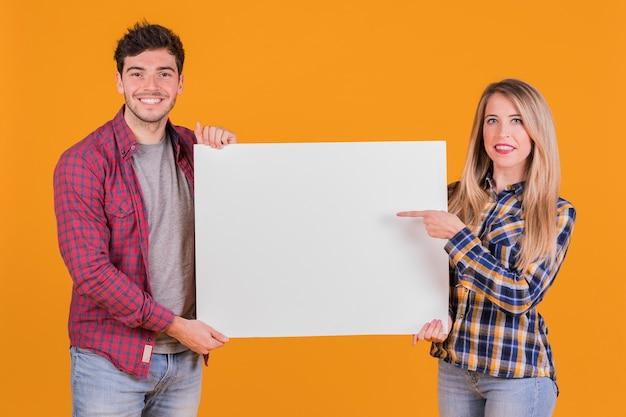 Jonge vrouw die haar vinger op aanplakbiljetholding richten door zijn vriend tegen oranje achtergrond Gratis Foto