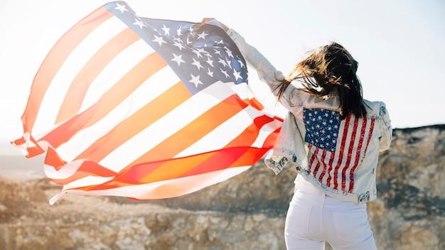 Jonge vrouw die handen met amerikaanse vlag opheft Gratis Foto