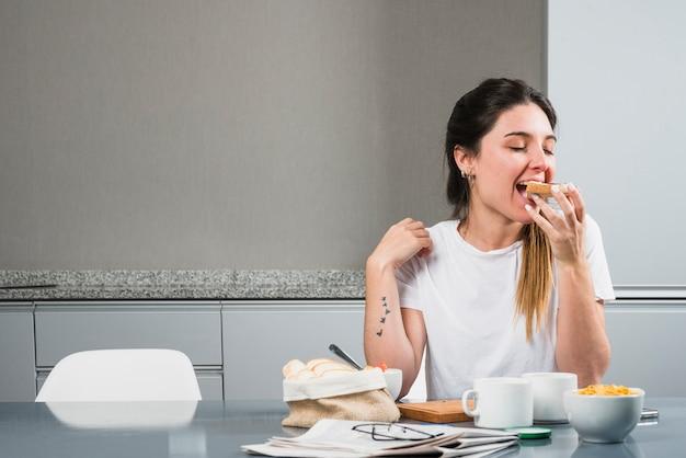 Jonge vrouw die het brood eet bij ontbijt Premium Foto