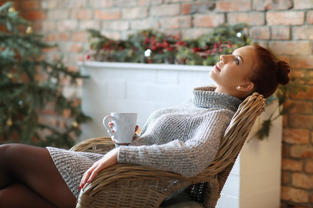 Jonge vrouw die hete thee op de bank drinkt Gratis Foto