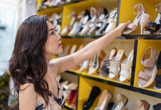 Jonge vrouw die hoge hielschoenen in winkel winkelt Premium Foto