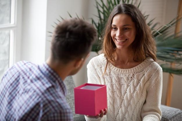 Jonge vrouw die huidig open giftdoos maakt aan echtgenoot maakt Gratis Foto