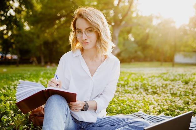 Jonge vrouw die iets in het notitieboekje in het park schrijft Premium Foto