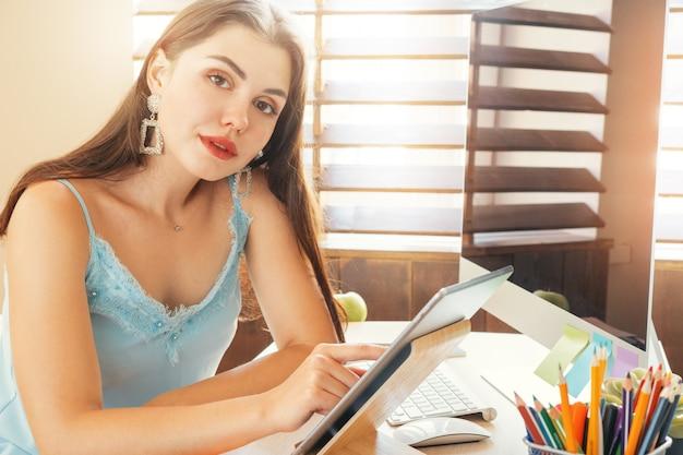 Jonge vrouw die in bureau werkt dat computer met behulp van, die bij bureau zit Premium Foto