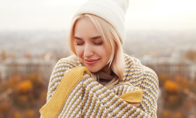 Jonge vrouw die in deken op platteland verpakt Premium Foto