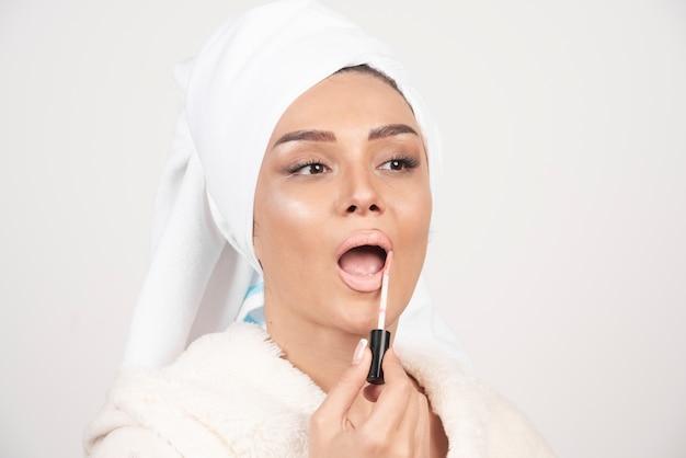 Jonge vrouw die in een badjas een lippenstift toepast. Gratis Foto