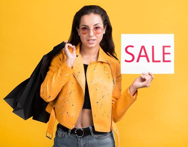 Jonge vrouw die in geel leerjasje een verkoopbanner houdt Gratis Foto