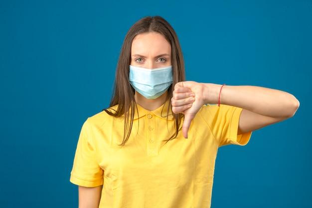 Jonge vrouw die in geel poloshirt en medisch beschermend masker duimen neer ondertekenen ernstig bekijkend camera op geïsoleerde blauwe achtergrond ondertekenen Gratis Foto
