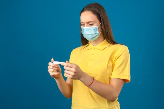 Jonge vrouw die in geel poloshirt en medisch beschermend masker thermometer met ernstig gezicht op geïsoleerde blauwe achtergrond bekijken Gratis Foto