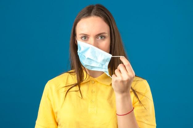Jonge vrouw die in geel poloshirt medisch beschermend masker opstijgen die camera met ernstig gezicht op geïsoleerde blauwe achtergrond bekijken Gratis Foto